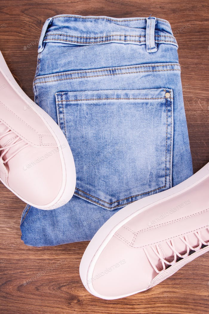 Womanly leather pink shoes and jeans pants on rustic board