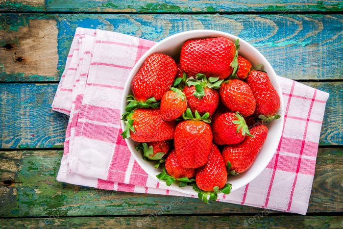 Fresh ripe organic strawberries in a white bowl top view