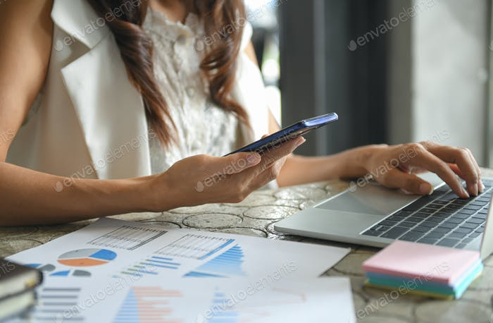 Hand of a business woman is using a mobile phone to find information.