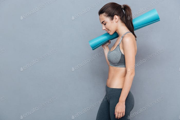 Cheerful beautiful fitness woman holding yoga mat and looking away