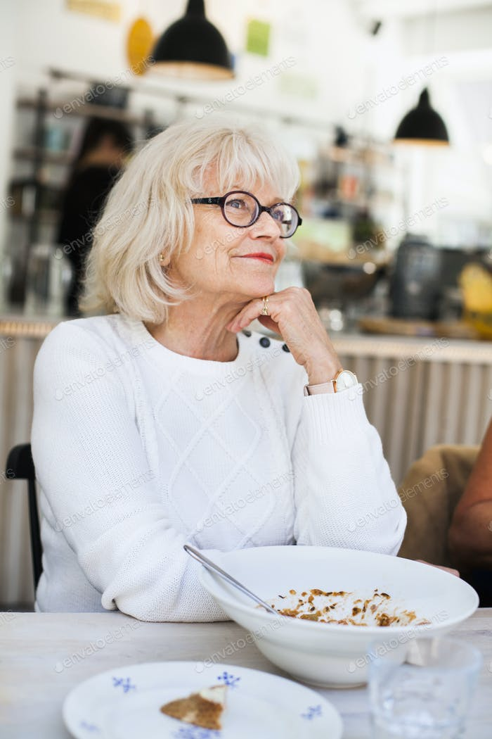 Smiling senior woman sitting and day dreaming in restaurant
