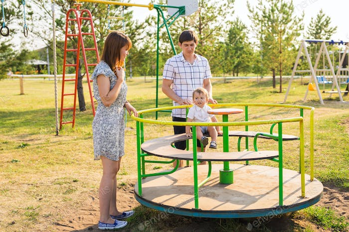 playful child with parents at the playground outdoor. Mom, dad and child.