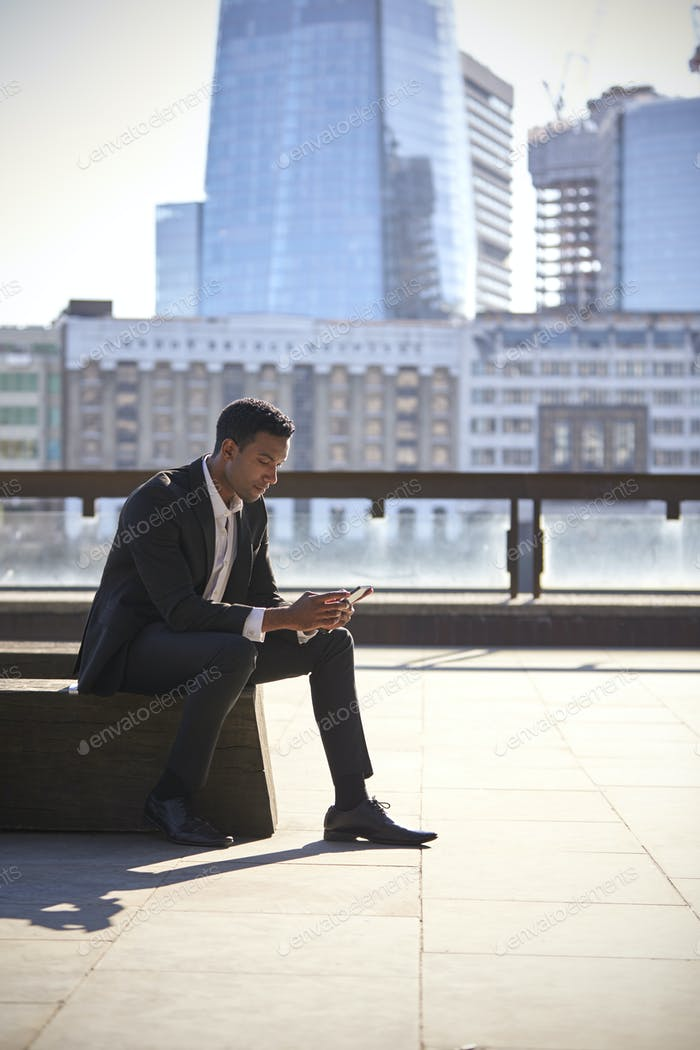 Millennial black businessman sitting using a smartphone in London