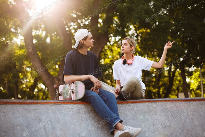 Beautiful girl with headphones and young guy with skateboard tho
