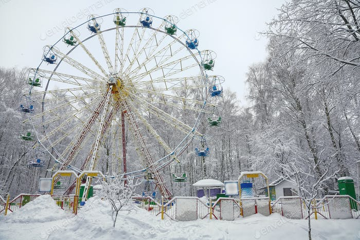 Snow covered Ferris wheel  surrounded by snowcovered trees