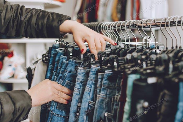 Fast Fashion-Konzept Frau wählt Jeans in einem Geschäft. Viele Klamotten im Laden. schnelle Mode