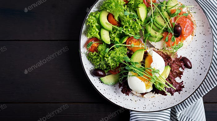 Healthy breakfast. Sandwiches with cream cheese, avocado, boiled egg and smoked salmon on plate