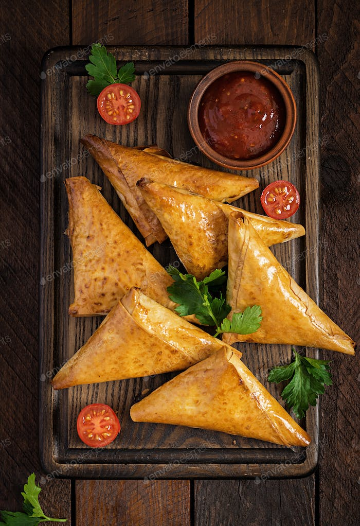Asian food. Samsa (samosas) with chicken fillet and cheese on wo