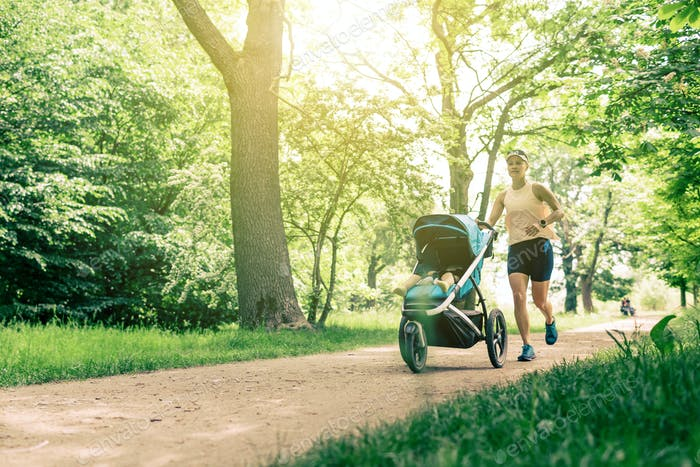 Running woman with baby stroller enjoying summer in park