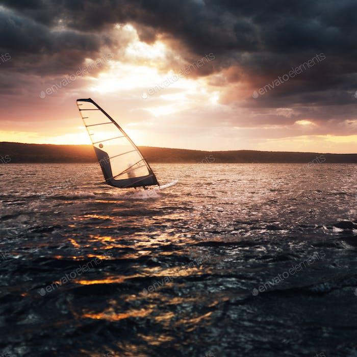 Windsurfen auf einem See bei Sonnenuntergang.