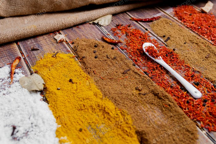 Cuchara blanca con azafrán cerca de diferentes especias coloridas