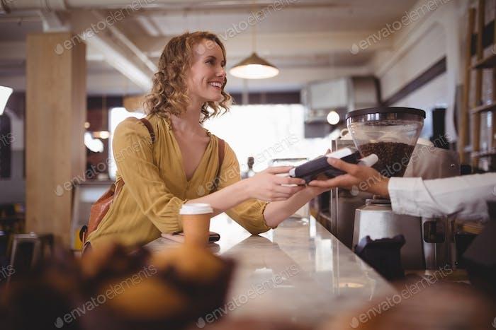 Lächelnd schöne weibliche Kunden Zahlung durch Karte am Schalter