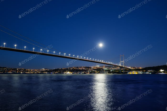 Bosphorus Bridge illuminated by lights and moon at night