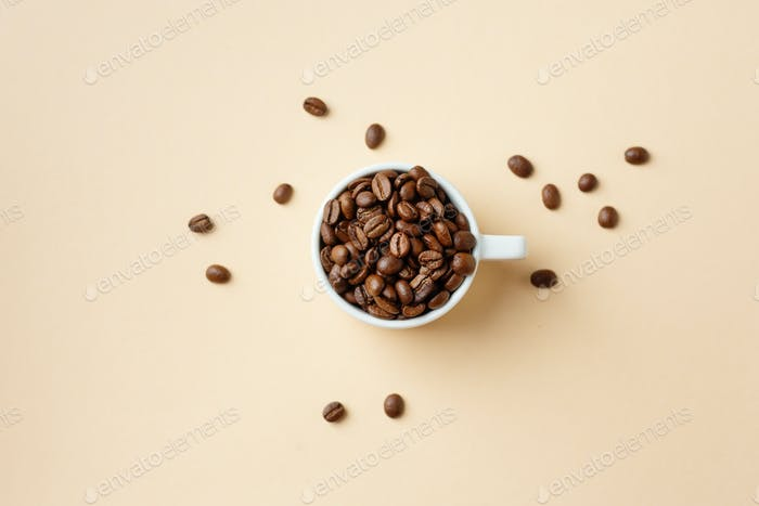 Coffee beans in cup on pastel