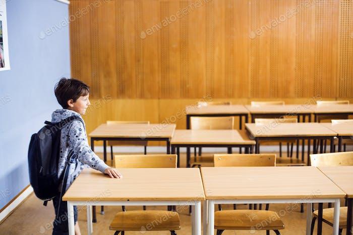 Niño llevando mochila mientras está de pie en el aula