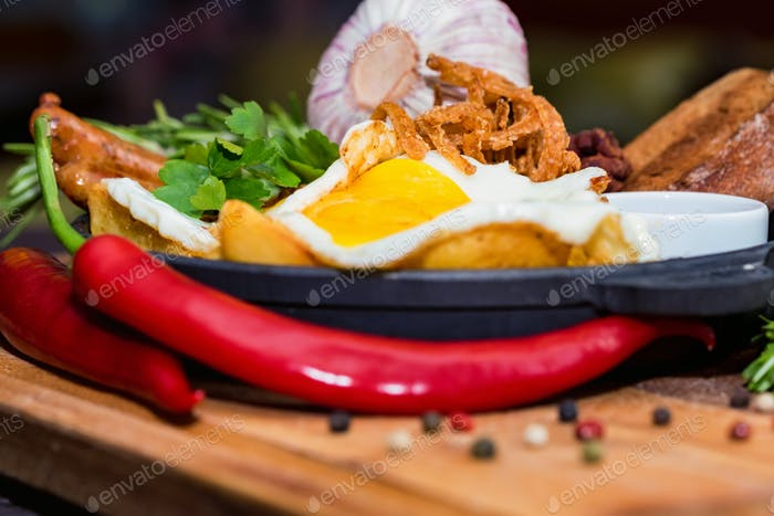 Meal with fried egg, sausages, beans, onion rings, chili pepper and sauce