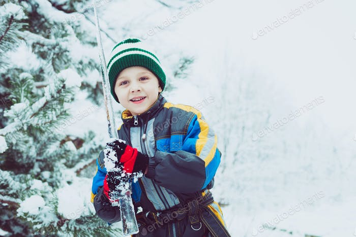 Happy little boy playing  on winter snow day.