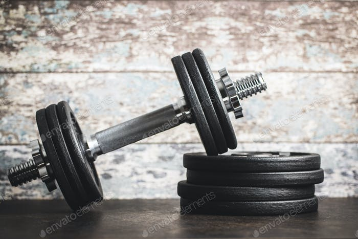 Iron dumbbells before old wooden wall.