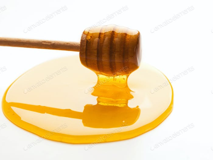 Honey and wooden dipper isolated on white