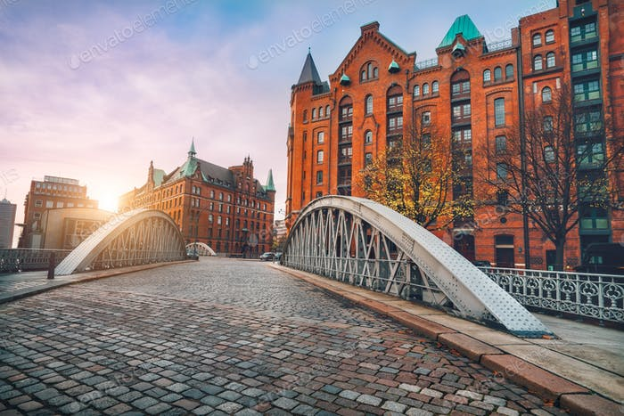 Arch bridge over alster canals with cobbled road in historical Speicherstadt of Hamburg, Germany