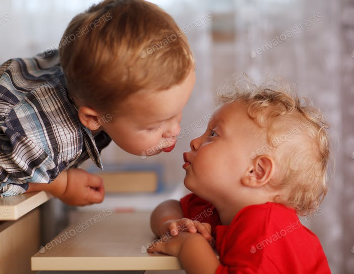 Cute siblings. Two little brothers are kissing