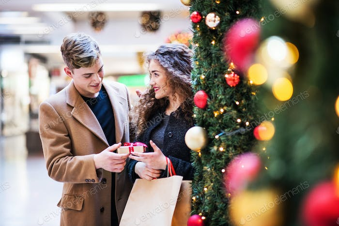 A young man giving a present to his girfriend in shopping center at Christmas.