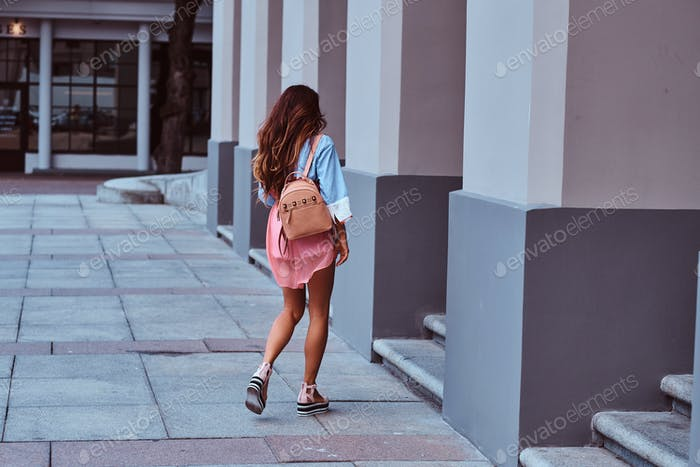 Beautiful middle aged woman with long brown hair dressed in trendy clothes walks on the street.