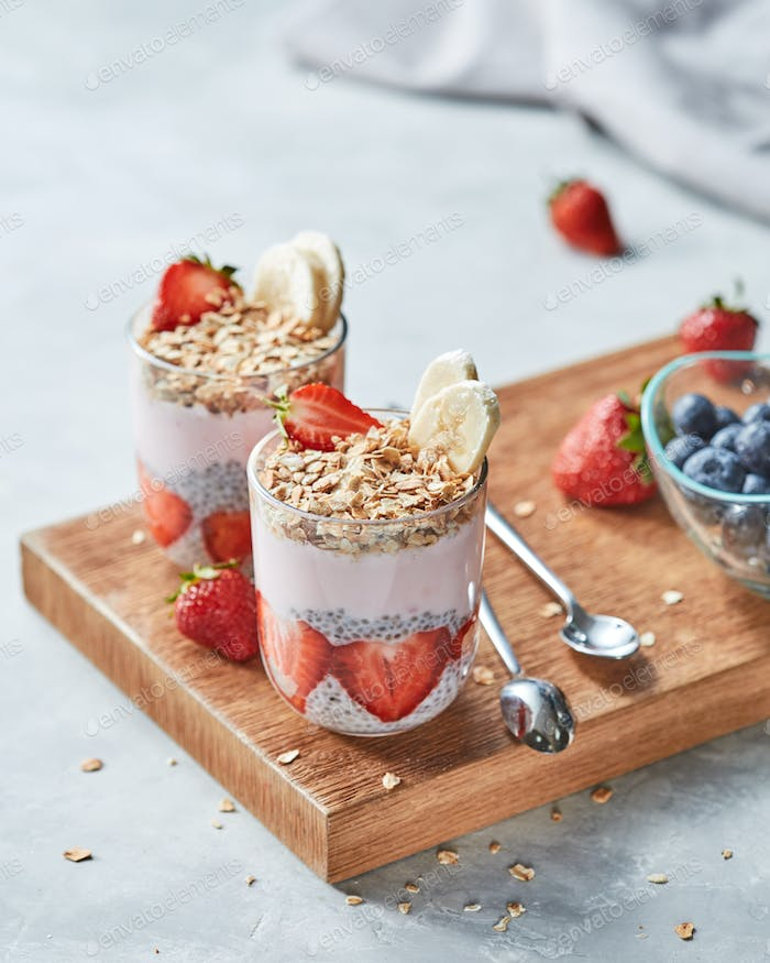 Granola, halves of strawberries, banana, chia seeds with yogurt in a glasses on a wooden board on a
