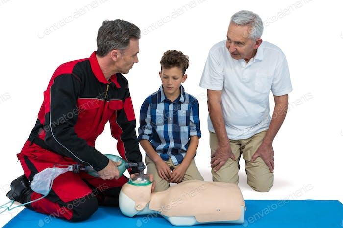 Paramedic training cardiopulmonary resuscitation to senior man and boy