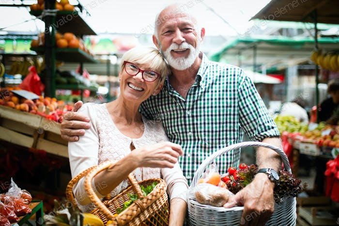 Mature shopping couple with basket on the market. Healthy diet