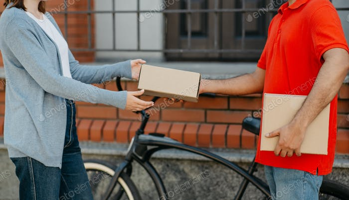 Online ordering. Client received package from bicikle courier in uniform, near front door