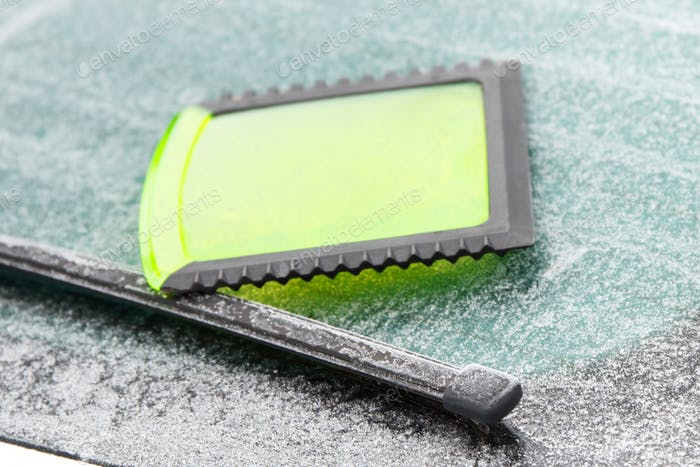 Green ice scraper on car windscreen in winter