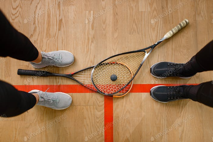 Female players legs and squash rackets, top view