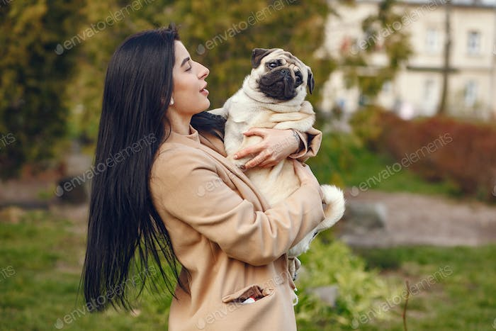 Brunette in a brown coat walks with pug