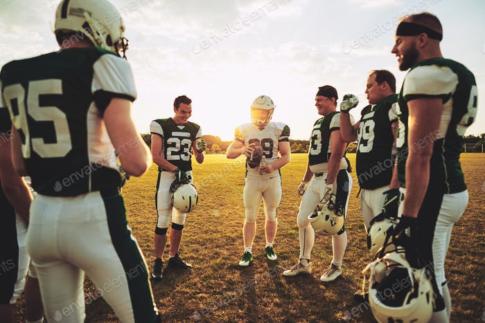 American football quarterback standing with his teammates discussing strategy
