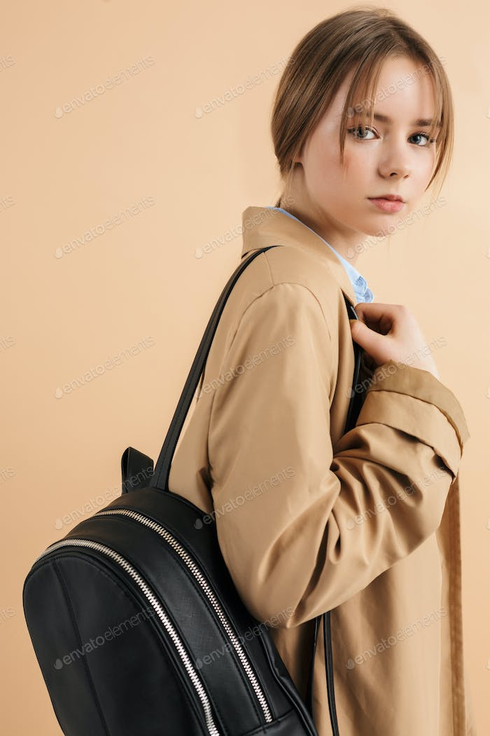 Young dreamy girl in trench coat with backpack on shoulder thoughtfully looking in camera