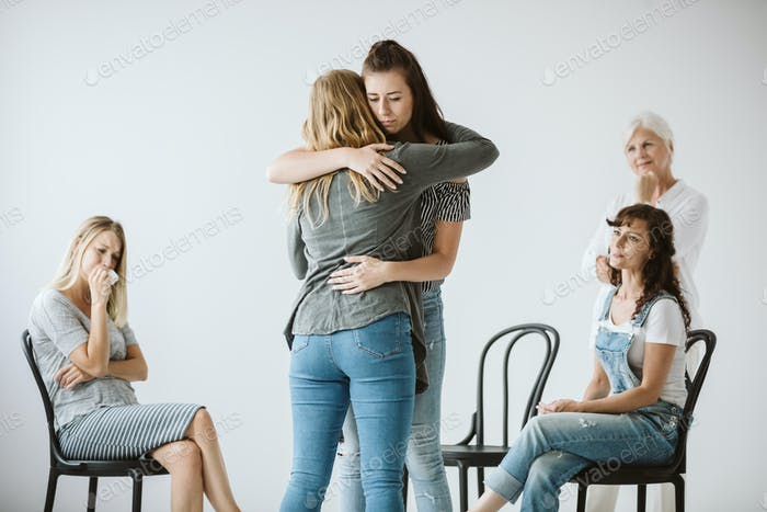 Sad women with depression are hugging each other during group psychotherapy