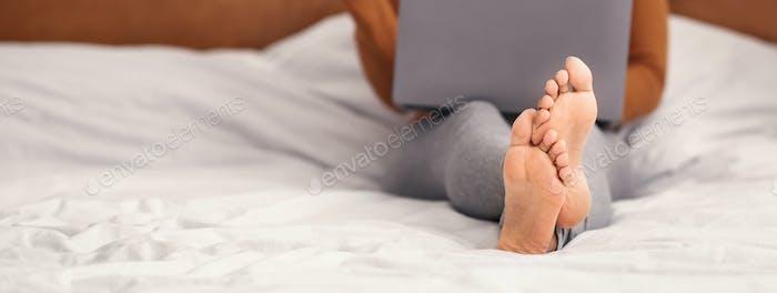 Unerkennbare Frau mit Laptop sitzt auf Bett im Schlafzimmer, Panorama