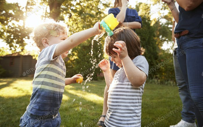 Boy Pouring Water Over Friends Head In Garden