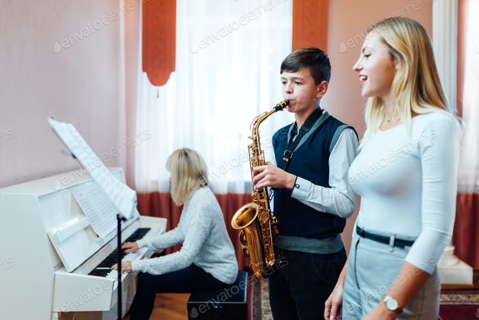 Boy student learns to play the saxophone in a music lesson to accompaniment of the piano.