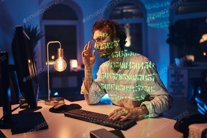 Профессиональный программист делает свою работу на компьютере в темном офисе