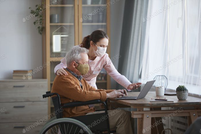 Disabled Senior Man Using Laptop with Caregiver Assisting