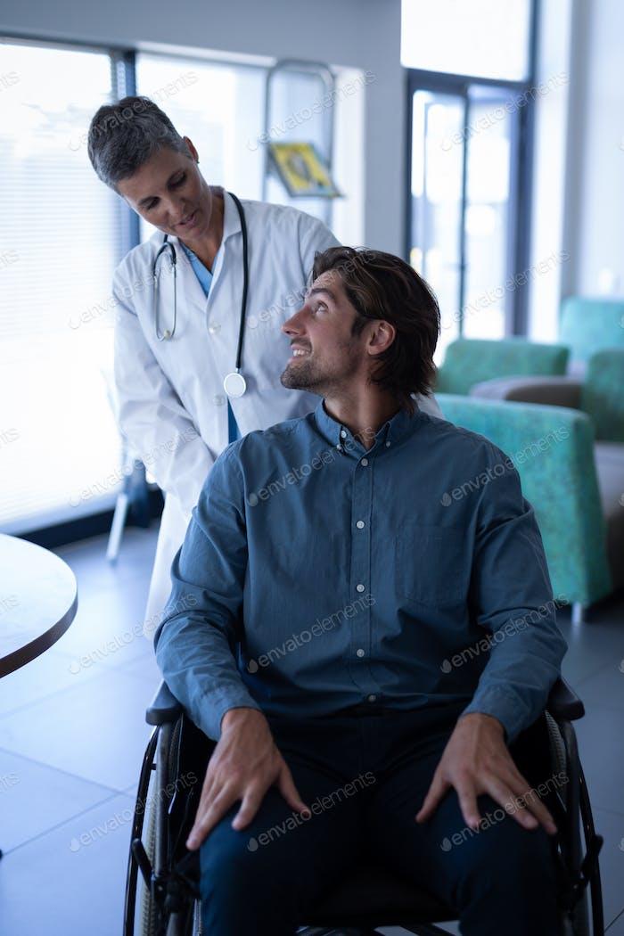 Kaukasische Ärztin im Gespräch mit behinderten kaukasischen Patienten im Rollstuhl in Klinik im Krankenhaus
