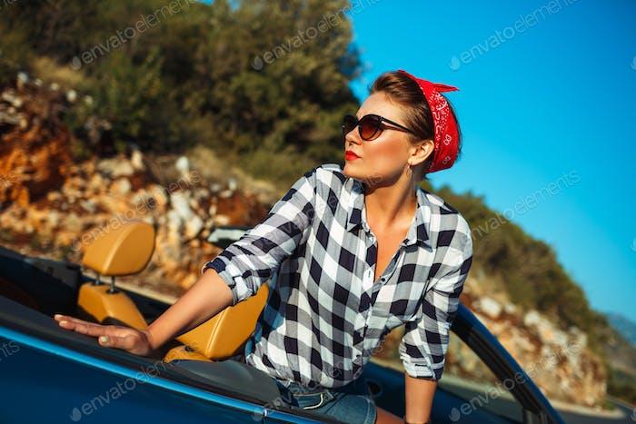 Beautiful pin up woman sitting in cabriolet, enjoying trip on lu