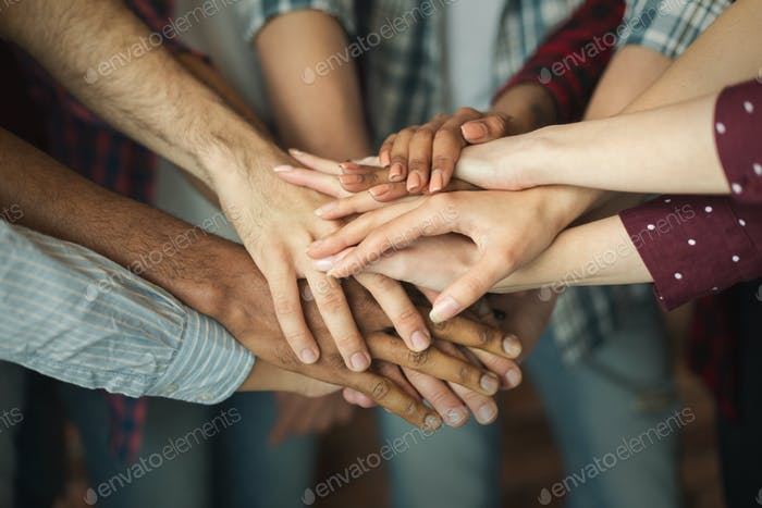 Group of friends holding hands together
