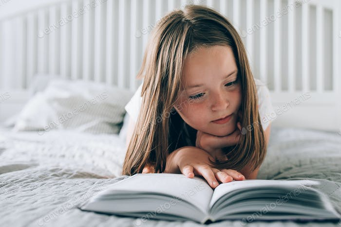 Pretty girl 8-9 years old lies on bed, reading the book. Comfort, cozy home concept. Lifestyle.