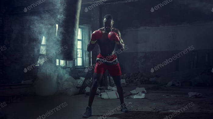 Hand of boxer over black background. Strength, attack and motion concept