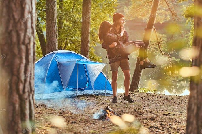 Glückliche Paar Wanderer, die Spaß in der Nähe eines Lagerfeuers im Lager im Wald haben.