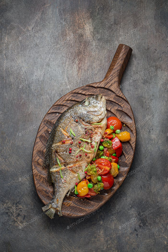 Sea bream fish with vegetables on cutting board, copy space