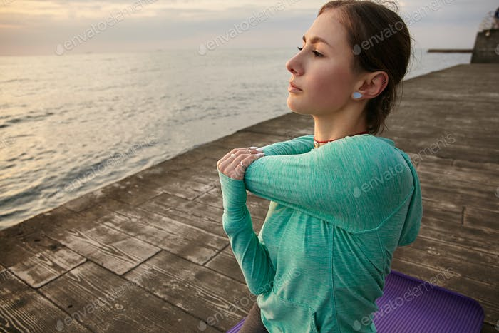 Sporty young woman dressed in bright sport wears, trains at the seaside, makes morning stretching
